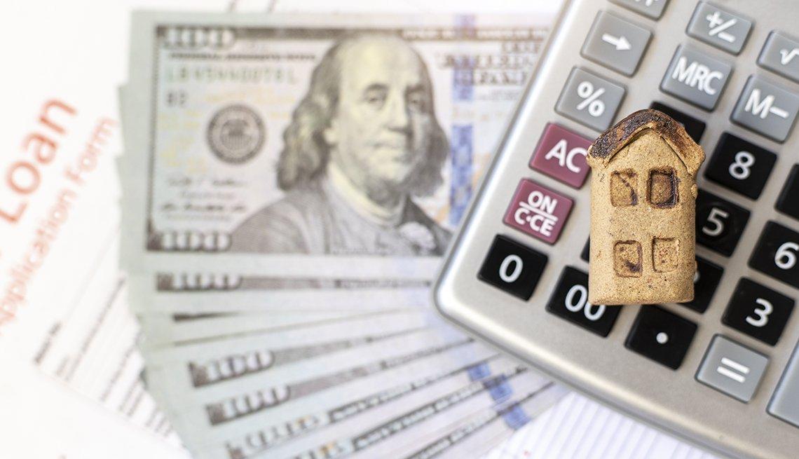 Casa en una miniatura sobre una calculadora, billetes de 100 dólares, y un formulario de préstamo.