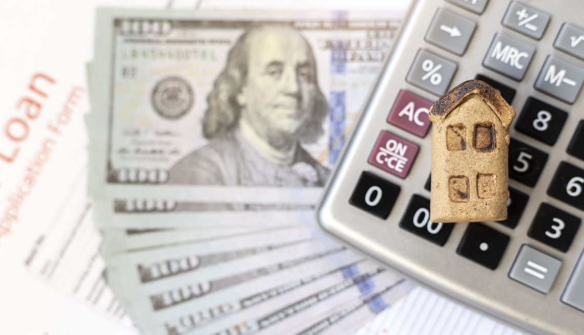 finance display of miniature home calculator hundred dollar bills and home loan papers
