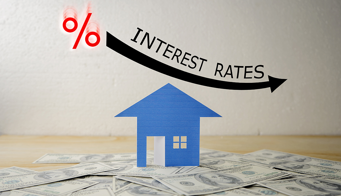 interest rates moving downwards illustrated by percentage sign, curved arrow, and a blue house standing on dollars