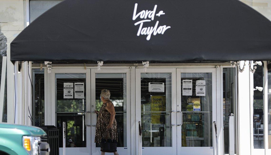Mujer frente a la entrada de la tienda por departamentos Lord & Taylor donde ve un anuncio de bancarrota por la pandemia.
