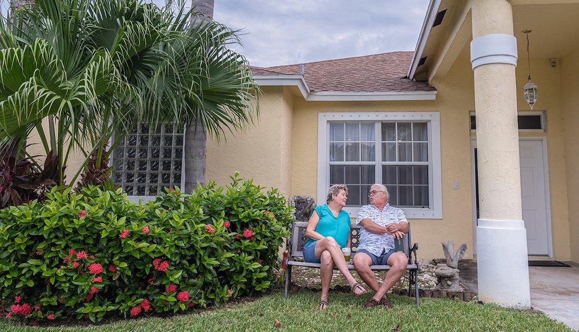 Paula y Dennis Arntz sentados en una banca a la entrada de su casa