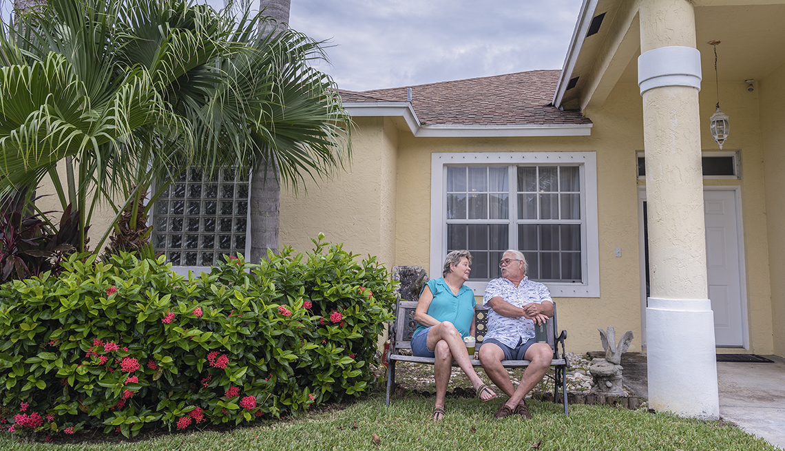 paula and dennis arntz sit on a bench in their front yard