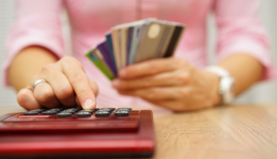 soft-focus woman holding handful of credit cards is adding up spending on a red calculator in foreground