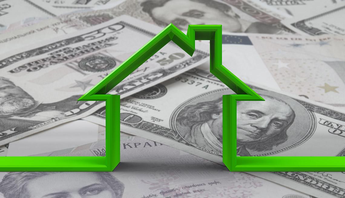 Silueta verde de una casa sobre dólares.