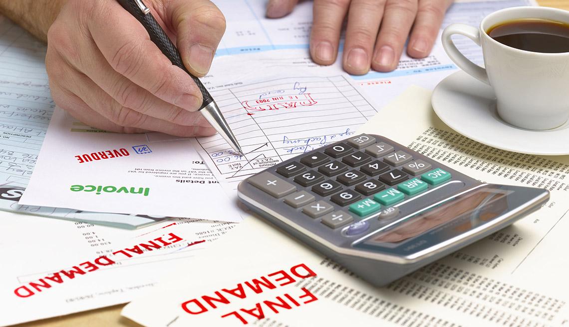 Manos de una persona revisando documentos con un lapicero, al lado de una calculadora y una taza de café.
