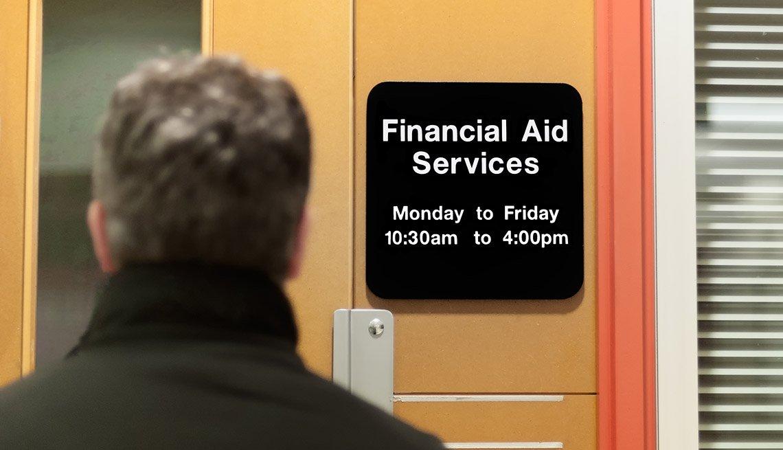 Estudiante mayor  frente  a la  oficina de servicios de ayuda financiera de una universidad