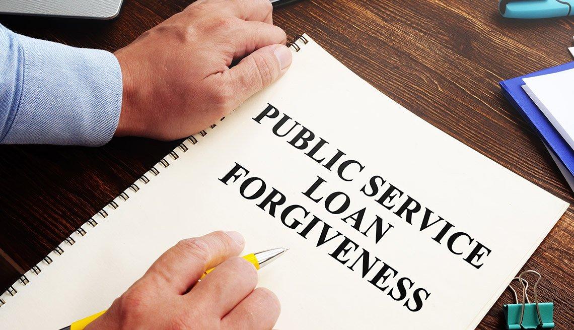 Hombre con las manos en un escritorio con un formulario que dice Servicio público para perdón de préstamos