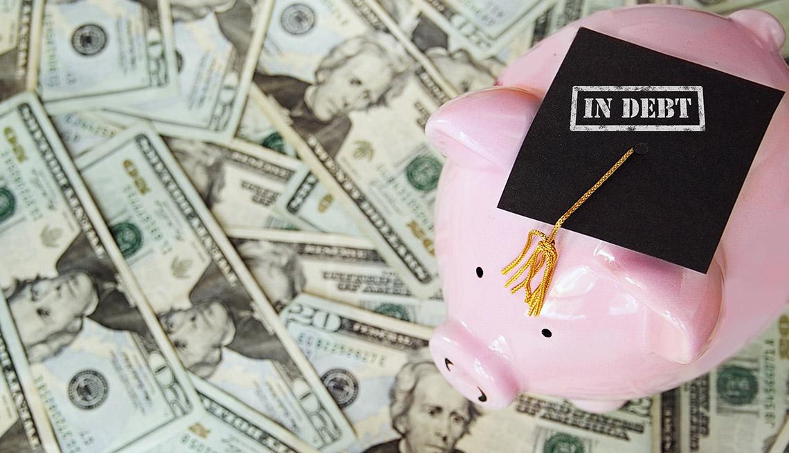 """a   piggy bank wearing a graduation cap marked """"debt"""" sits on a field of money"""