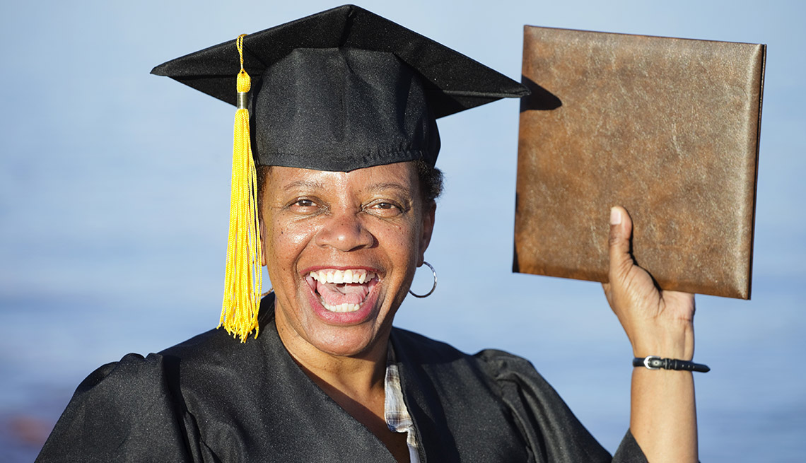 Happy portrait of a woman dressed in a graduation cap and gown holding up a diploma and smiling against a blue sky.