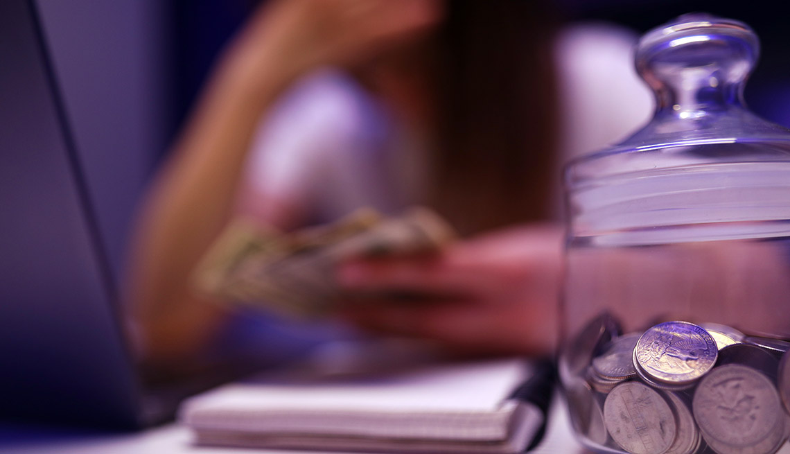 a soft focus image that looks melancholy, of a woman hunched over table holding money with jar of quarters in foreground.
