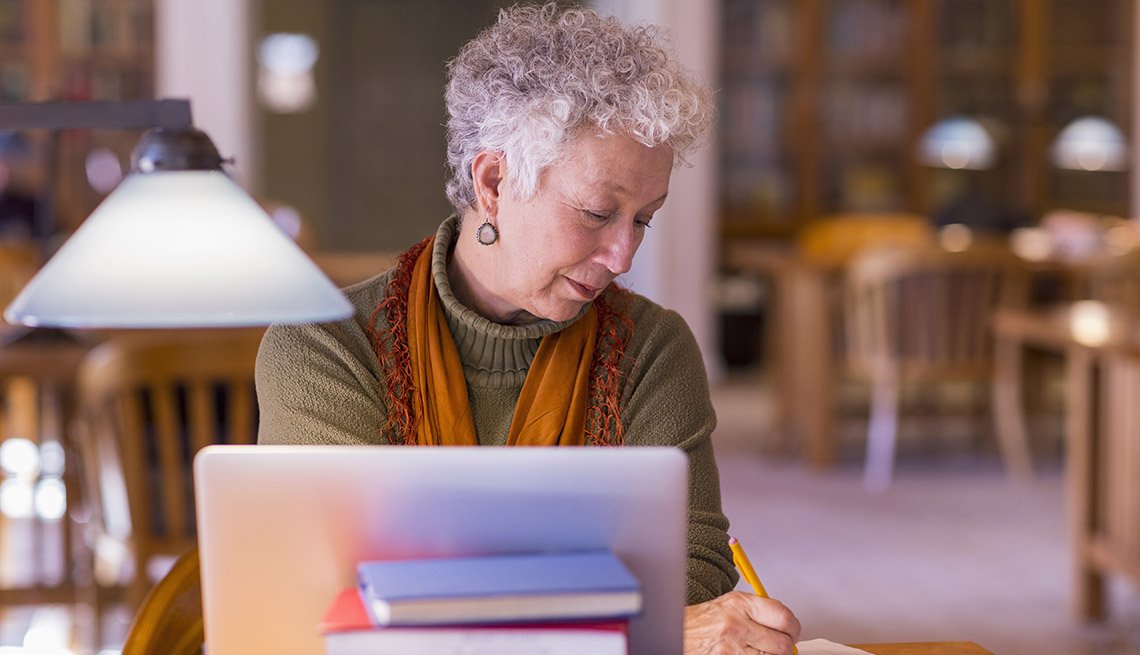 woman seated in library taking notes with laptop and stack of books in view