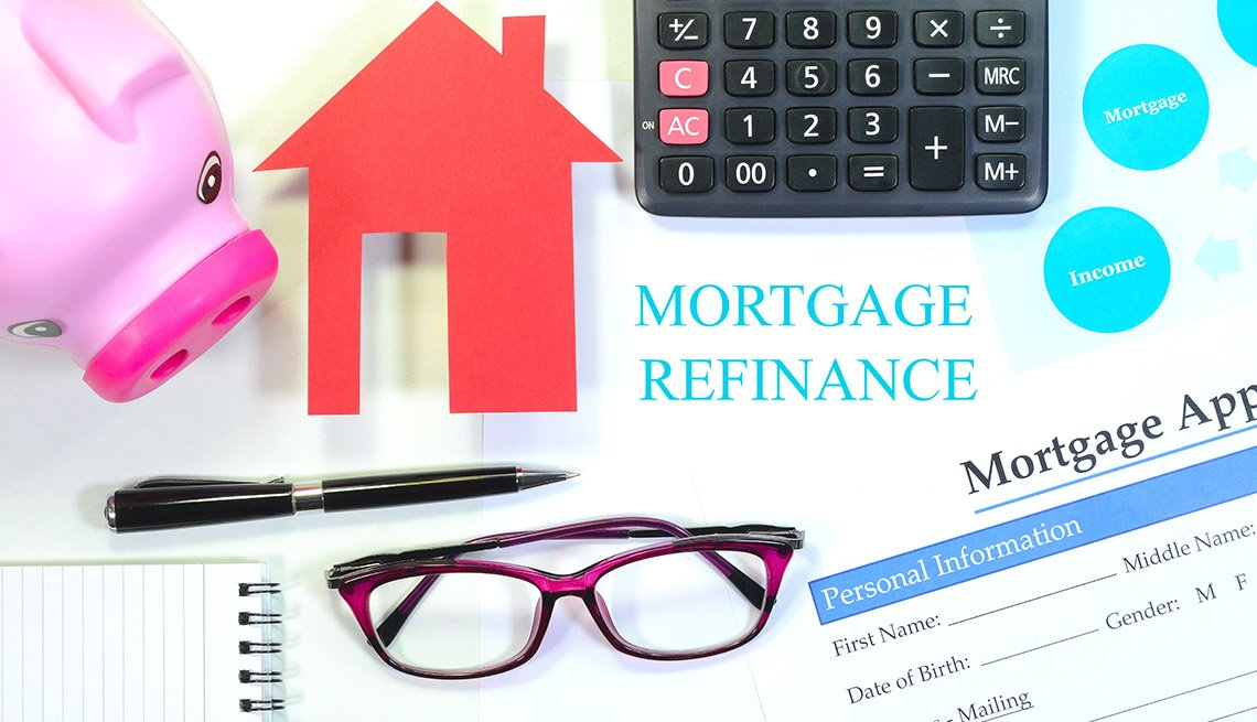 display of items used when considering refinancing the mortgage including eyeglasses, calculator, mortgage application, home and a piggy bank.