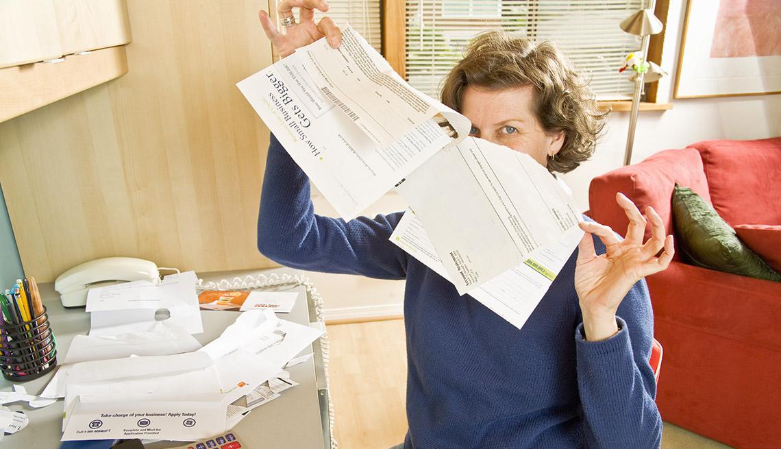 Mujer en la oficina de su casa rompiendo facturas viejas