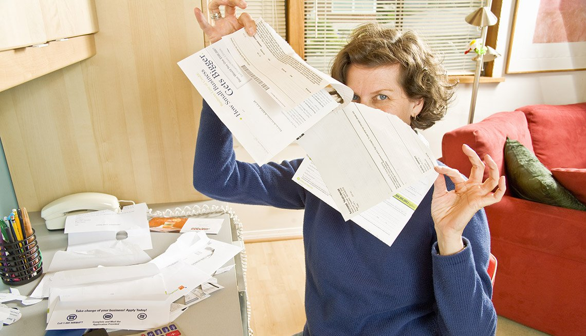 woman seated in home office looks relieved as she rips up a bill from a big stack on her desk