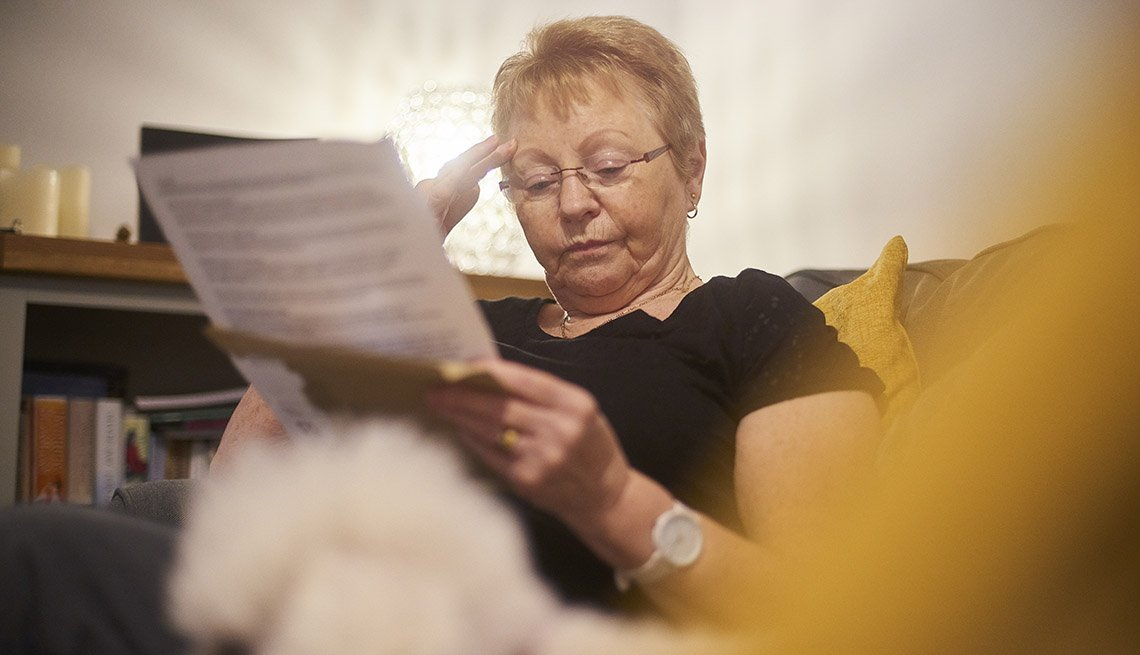 worried woman reading through document with her head in her hands