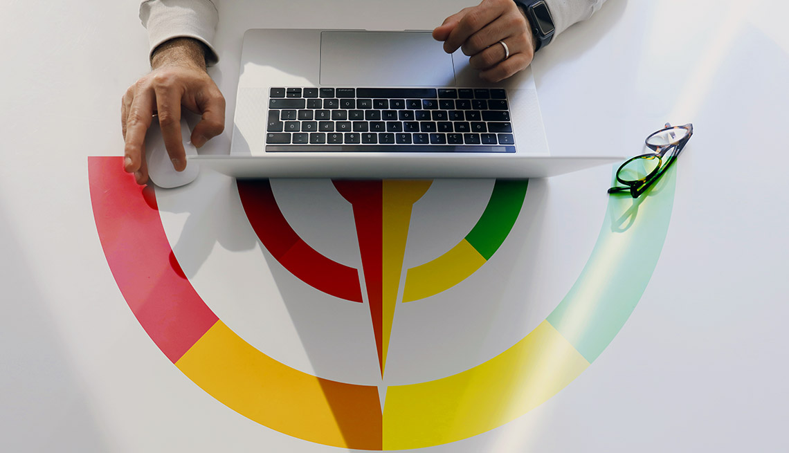 high angle close-up view of hands using laptop with an illustrated credit score meter displayed on the tabletop