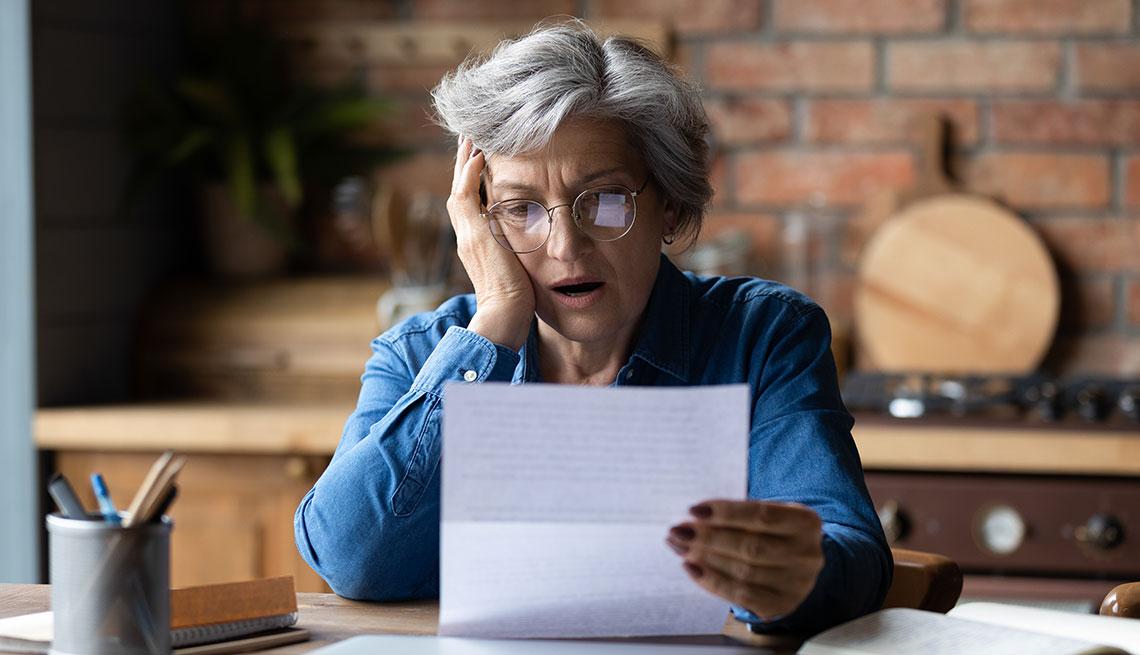 Mujer con cara de asombro pone su mano sobre el cachete mientras que con la otra sostiene una factura
