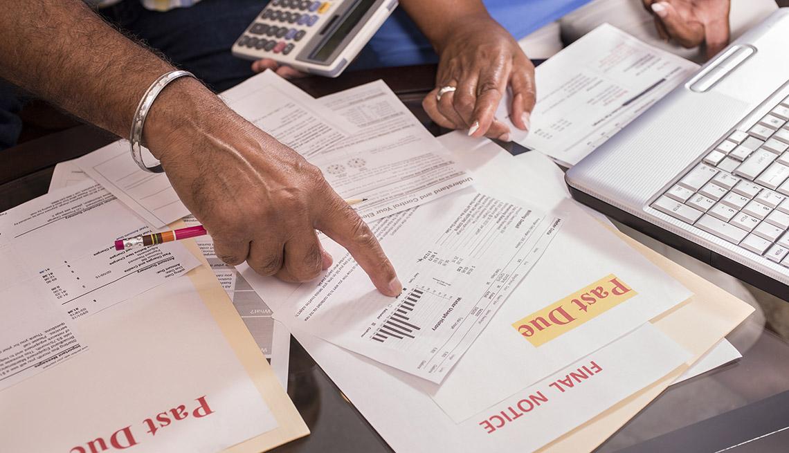 Manos sobre unas facturas vencidas en una mesa.