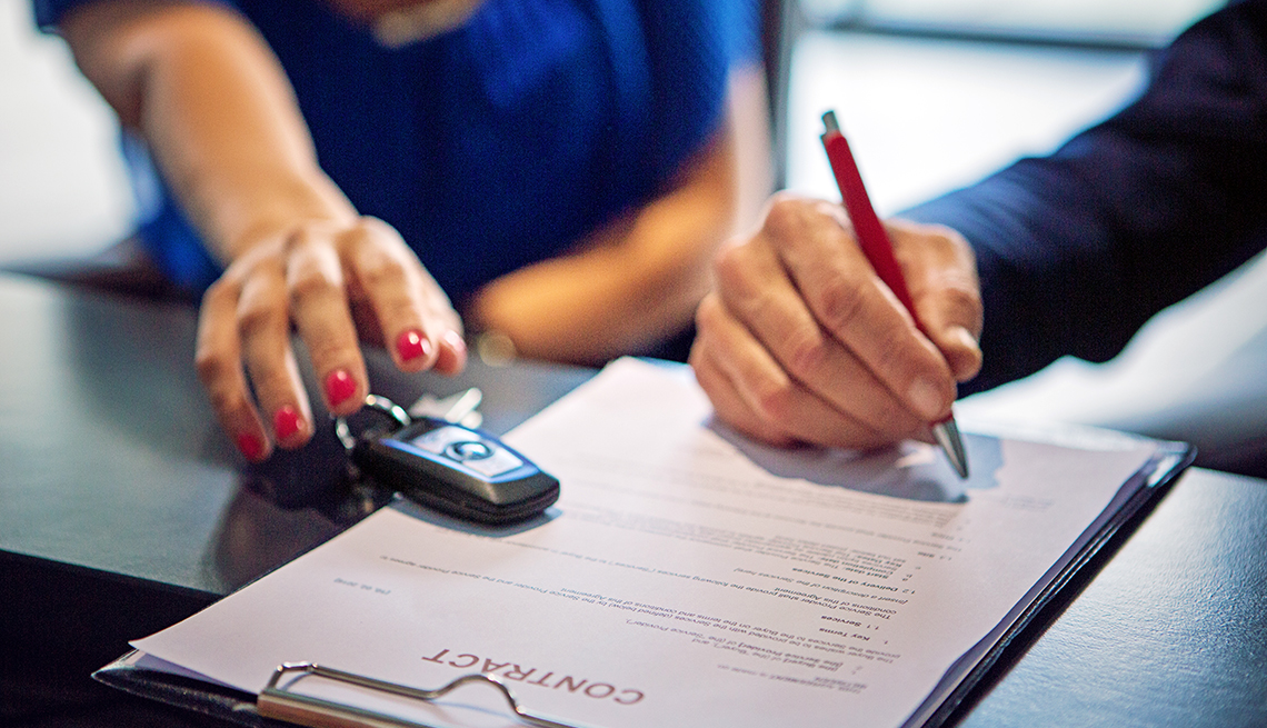 closeup of a woman's hand reaching over car keys as man's hand is signing a contract