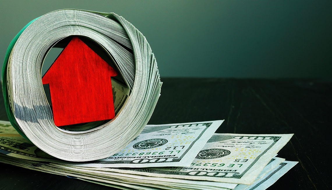 a minature wooden red house is wrapped inside a roll of hundred dollar bills on a dark green background
