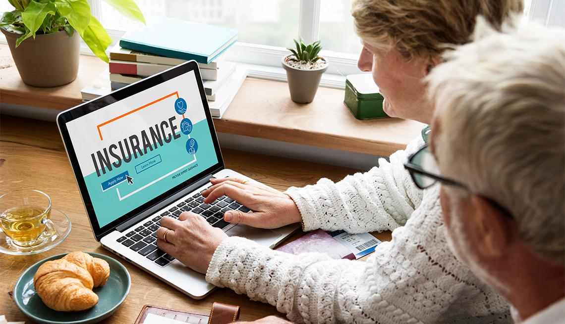 Pareja buscando seguros en línea a través de una computadora portátil.