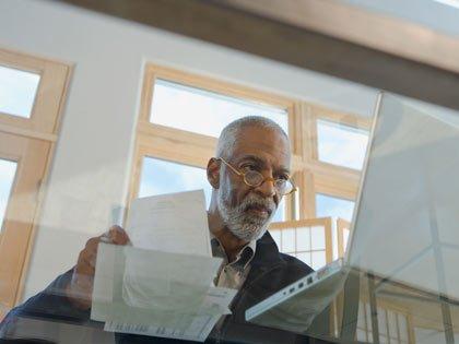 man paying bills online with laptop