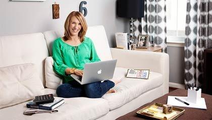 Bev Hollis se sienta en el sofá con un computador en sus piernas