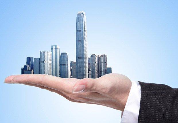 Hombre sosteniendo una ciudad en su mano - Movimientos malos de dinero
