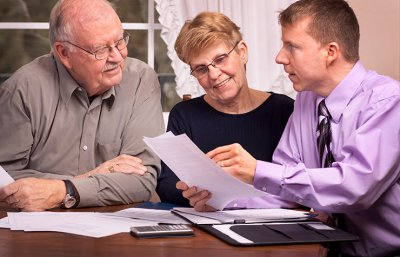 A mature couple discuss a living will with an adviser