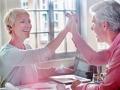 Pareja mayor sentada en una mesa y tomándose la mano en señal de victoria - Cómo preparase para una jubilación temprana