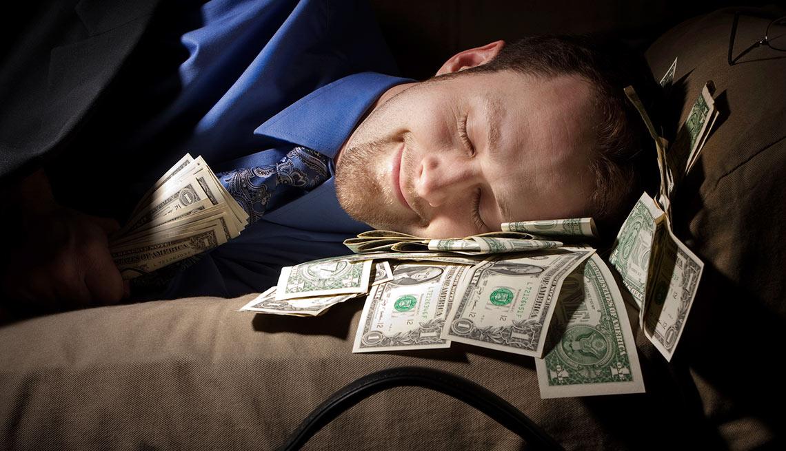 Hombre durmiendo al lado de unos billetes de dólar - Pecados capitales de las finanzas personales