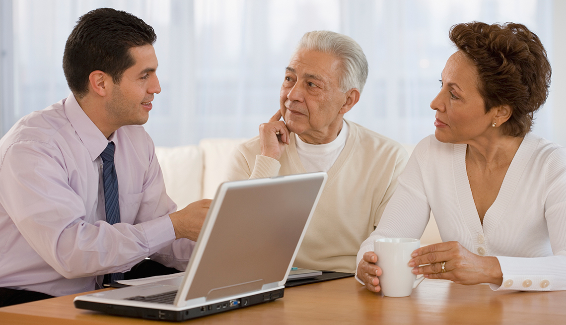 Hombre en corbata frente a un computador hablando con una pareja mayor - Errores frecuentes al comprar un negocio