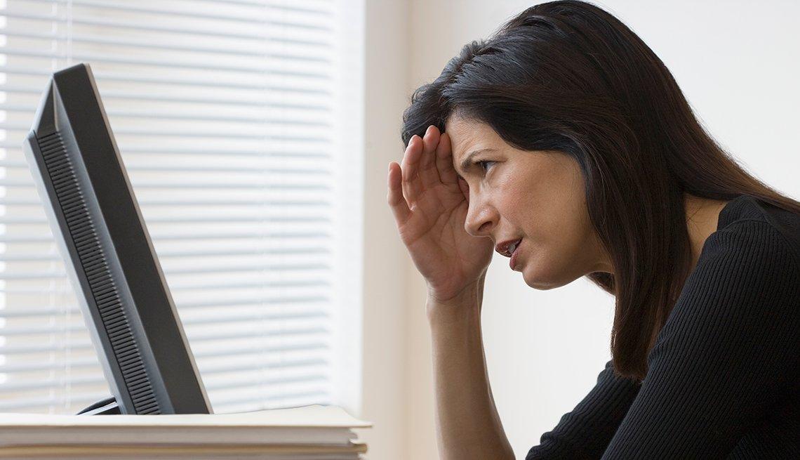 Mujer frente a una computadora con la mano en la frente - Errores frecuentes al comprar un negocio