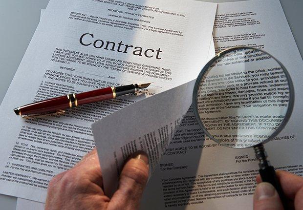 Manos con una lupa viendo un contrato - Errores frecuentes al comprar un negocio