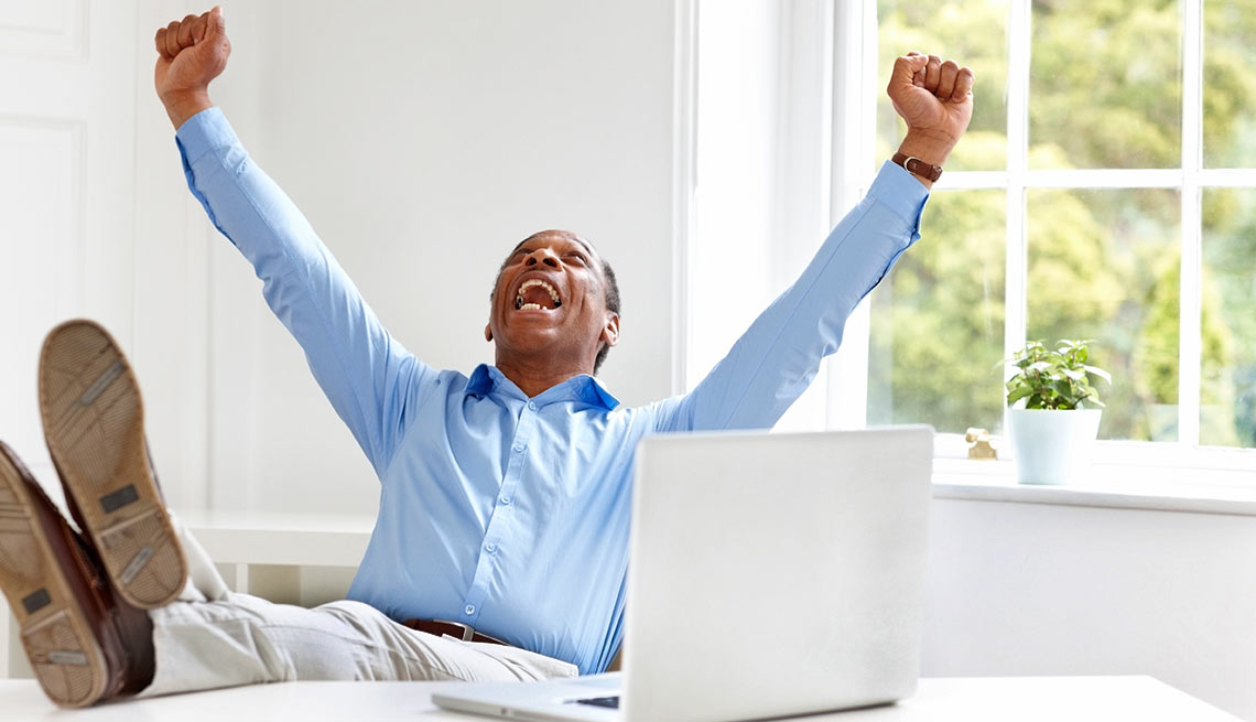 Seven Ways to Save More - Excited mature businessman celebrating success at his desk