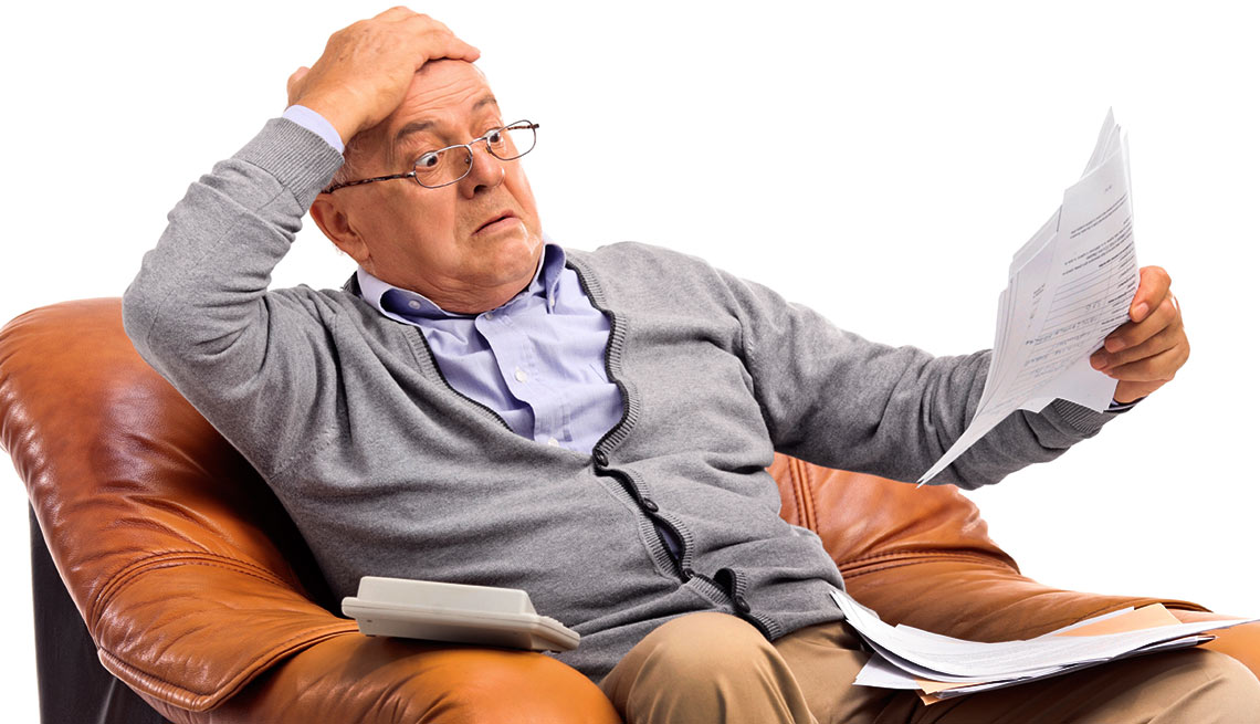 Shocked man looking at his bills in disbelief, mutual fund capital gains trap