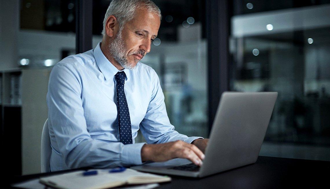 Hombre vestido con corbata y camisa frente a una computadora personal
