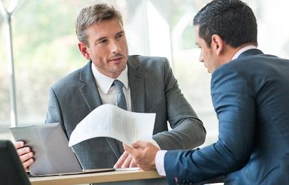 Dos hombres en traje de corbata frente a una computadora personal, presidente Trump pospuso regla de protección a inversores
