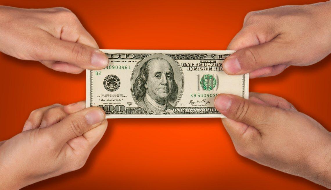 Manos de un hombre y una mujer estirando un billete de 100 dólares