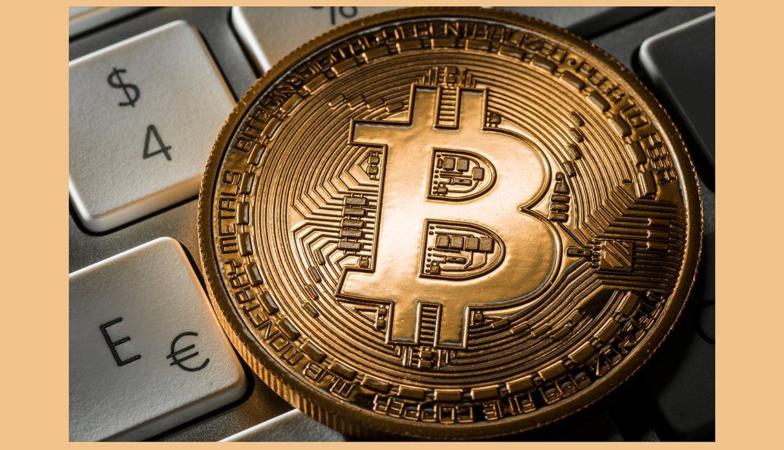 Ilustración de una moneda Bitcoin Illustration encima de un teclado con los símbolos del euro, y el dólar y aprende de los riesgos de esta moneda