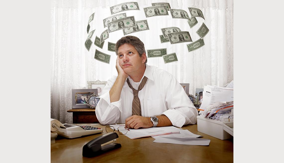 Hombre en una oficina y varios círculos de billetes de dólar dando vuelta a su cabeza, ¿estás ahorrando para el retiro?