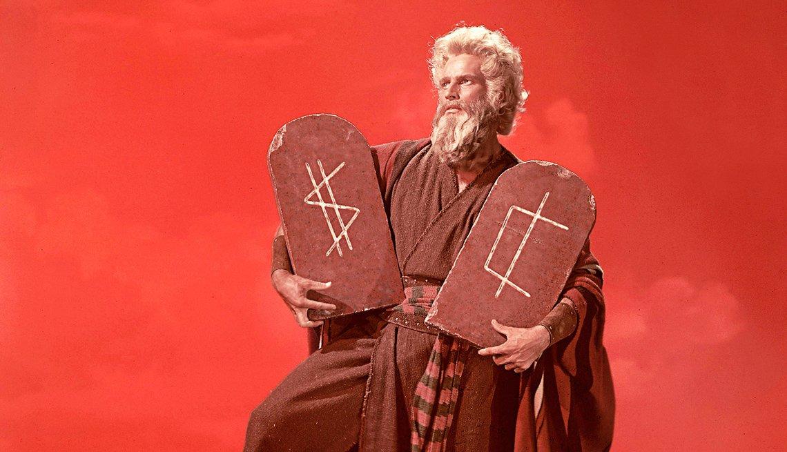 Imagen de Moisés sosteniendo las tablas de los mandamientos con signos de dólar y euro