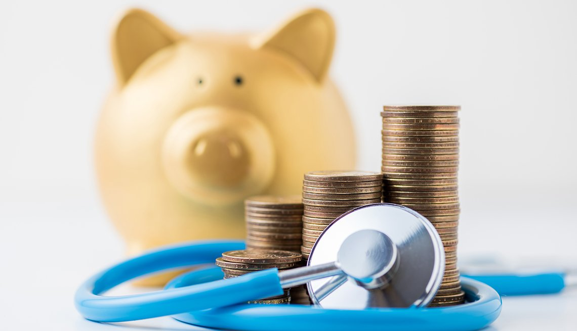 coins stack with stethoscope and gold piggy bank on white backgr