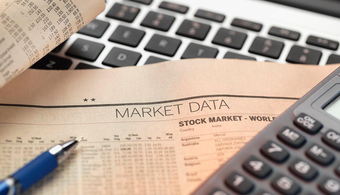 Hoja del mercado de valores sobre una computadora y una calculadora