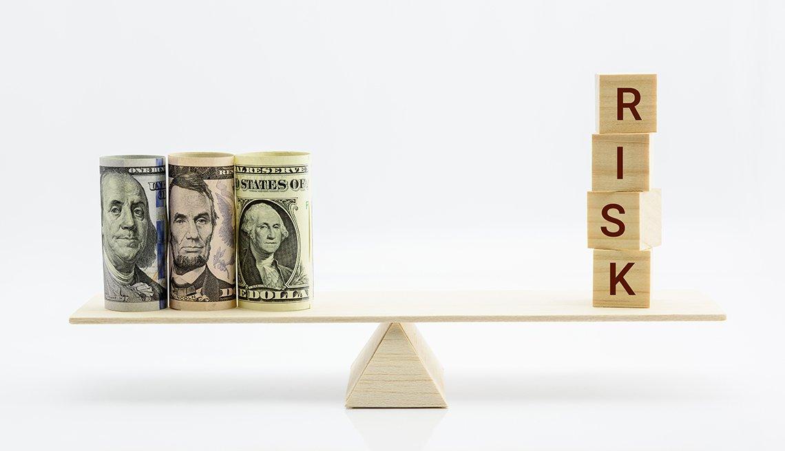 Balanza con dólares a un lado y la palabra riesgo en el otro.