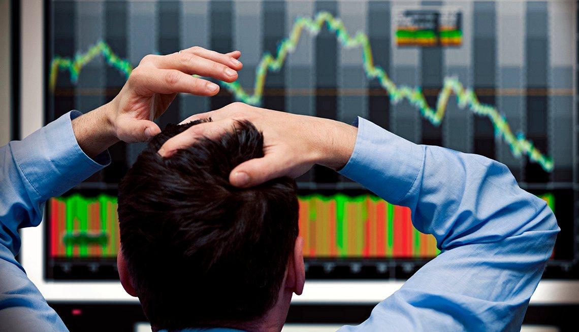 Un hombre se toma la cabeza mientras ve una pantalla con indicadores finacieros