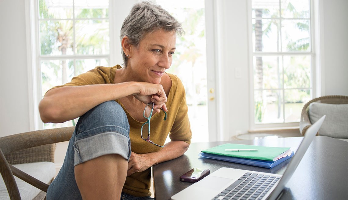 Woman in jeans looks at laptop