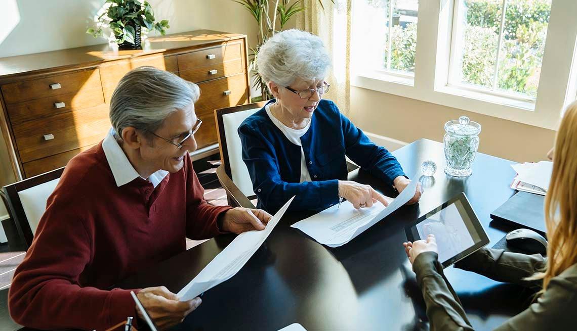 Pareja de adultos mayores con una asesora financiera en su oficina.