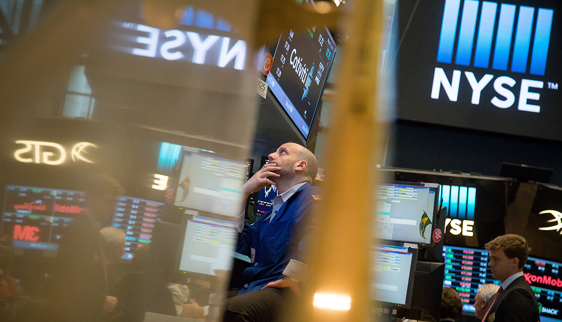 Wall Street trader looking up at screens