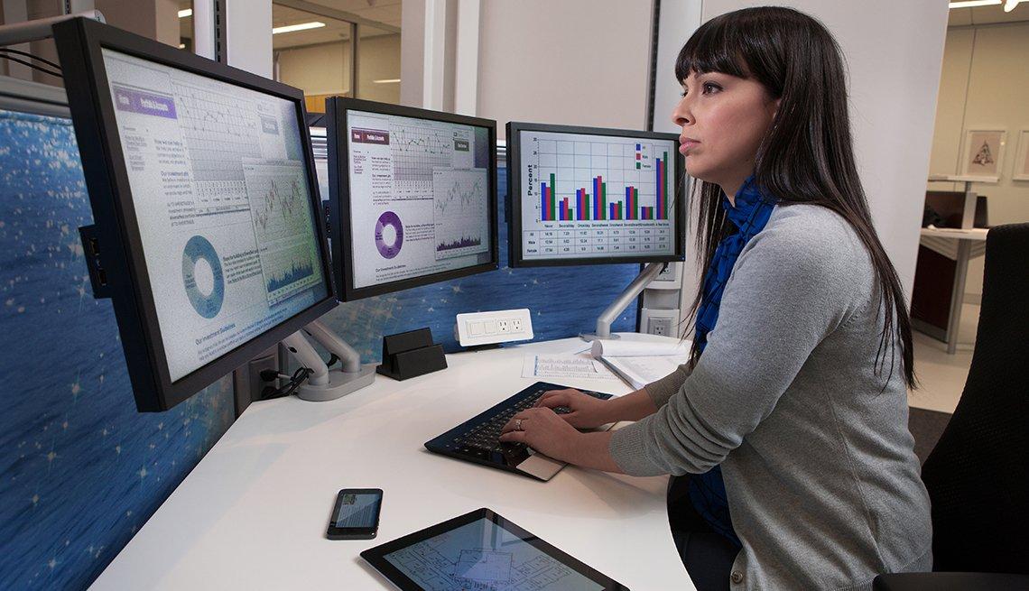 Analista financiero frente a tres pantallas de computadora.